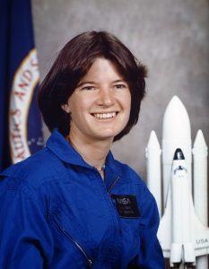Lächelnde Frau mit dunkelbraunen kurzen Haaren im blauen Raumfahrtsanzug, im Hintergrund ein weißes Raketenmodell