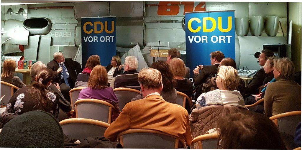 Viele Menschen sitzen in einem Raum vorne sind zwei CDU Banner