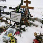 Grab von Anna Politovskaya im Schnee mit Blumen einem Holzkreuz und einem Foto von ihr.