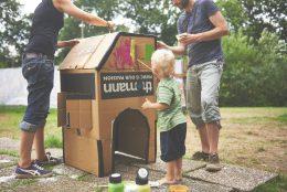Zwei Erwachsene bemalen ein Pappkarton Haus mit bunten Farben. In der Mitte steht ein blondes Kind und malt auch.