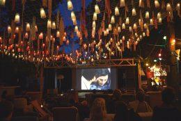 In ther unteren Hälfte des Bildes sitzen Personen auf Sesseln im freien und schauen auf eine große Leinwand in der Mitte des Bildes. In der oberen Hälfte des Bildes sieht man ein Dach aus Lichtern und bunten Tüchern. Durch das Dach sieht man die Umrisse von Bäumen und einen dunkelblauen Nachthimmel.