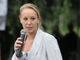 Junge Frau hält und spricht in ein Mikrophon.