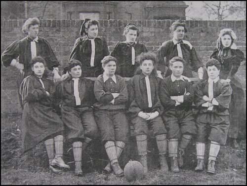 Altes Schwarz/Weiß Foto von 11 Frauen. Vor ihnen liegt ein Fußball.