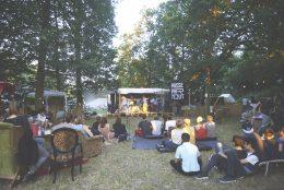 Vereinzelte Gruppen von Personen sitzen auf Matten und Sesseln und Sofas auf einer Wiese, sie sind von hinten fotografiert und schauen auf eine Bühne die auf Paletten steht. Darauf ist eine Band zu sehen. Daneben steht ein schwarzes Schild auf dem steht: Passe Par Tout. Drumherum stehen viele Bäume.