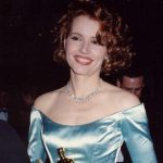 Lächelnde Frau in hellblauen Abendkleid mit dem Filmpreis Oscar in der Hand.