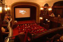 Kinosaal mit goldenen Tribünen und roten Sesseln