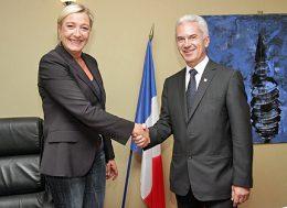 Frau und Mann geben sich vor französischer Flagge die Hand