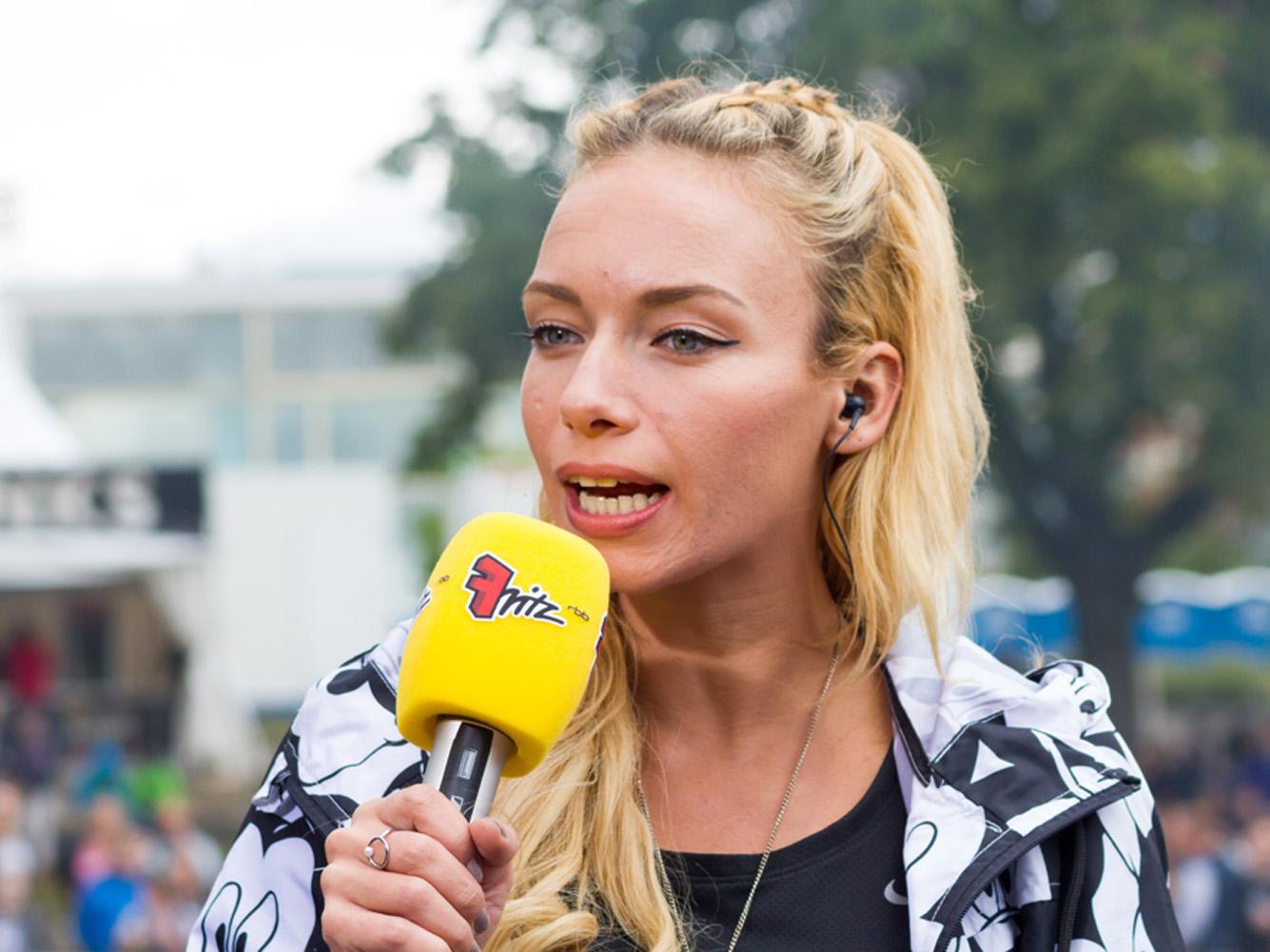 Frau mit gelben Mikrofon in der Hand im Gespräch