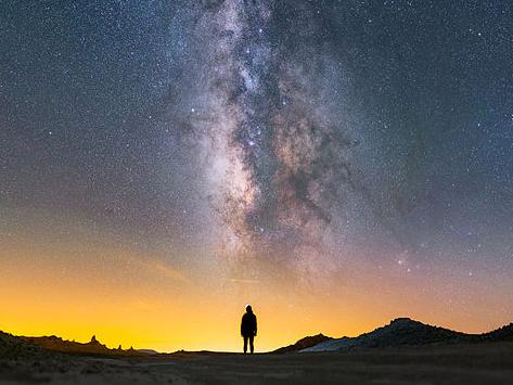 Person steht in der Wüste, über ihr der Sternenhimmel und die Milchstraße. Der Himmel leuchtet gelb und die zentral stehende Person ist nur als Silhouette zu erkennen.