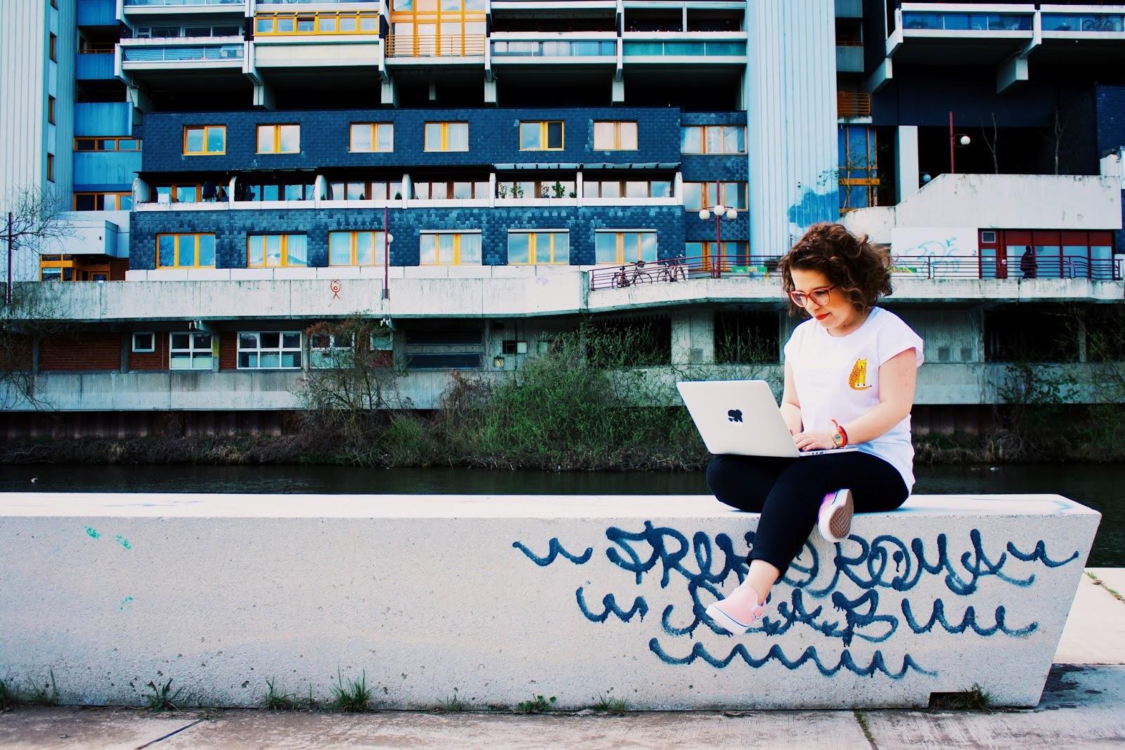 Frau am Laptop, sitzt auf einer Steinbank vor einem Flussufer, hinter dem sich ein Hochhaus abzeichnet