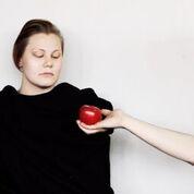 Eine junge Frau im schwarzen Gewand, der von einer ins Bild reichenden hand ein roter Apfel angeboten wird