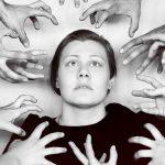 Junge Frau in schwarz-weiß umgeben von ins Bild greifenden Händen