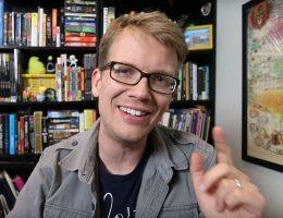 Junger blonder Mann mit schwarzer Brille namens Hank Green sitzt vor einem schwarzen, übervollen Bücherregal. Er lächelt in die Kamera und trägt ein graues Hemdn über einem schwarzen Shirt. Seine Hand mit ausgestrecktem Zeigefinger ist erhoben.