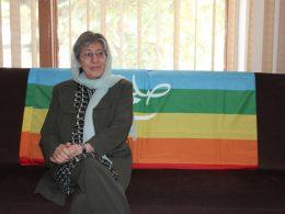 Sima Samar sitzt auf der linken Seiten eines Sofas. Über das Sofa ist eine Regenbogenflagge drapiert.