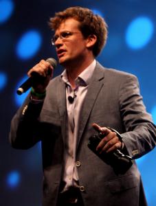 John Green, ein junger braunhaariger mann mit Brille, steht vor einer blaugepunkteten Leiwnand mit einem Mikrofon in der einen und einer Kamera in der anderen Hand. er trägt ein graues Jackett und ein weißes Hemd.