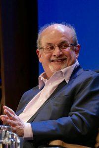 Der Autor Salman Rushdie sitzt auf einem Stuhl vor einem blauien Hintergrund während eines Interviews. Er hat einen grauen Haarkranz, eine Halbglatze, ein schwarzes Jacket, weißes Hemd und eine Brille.