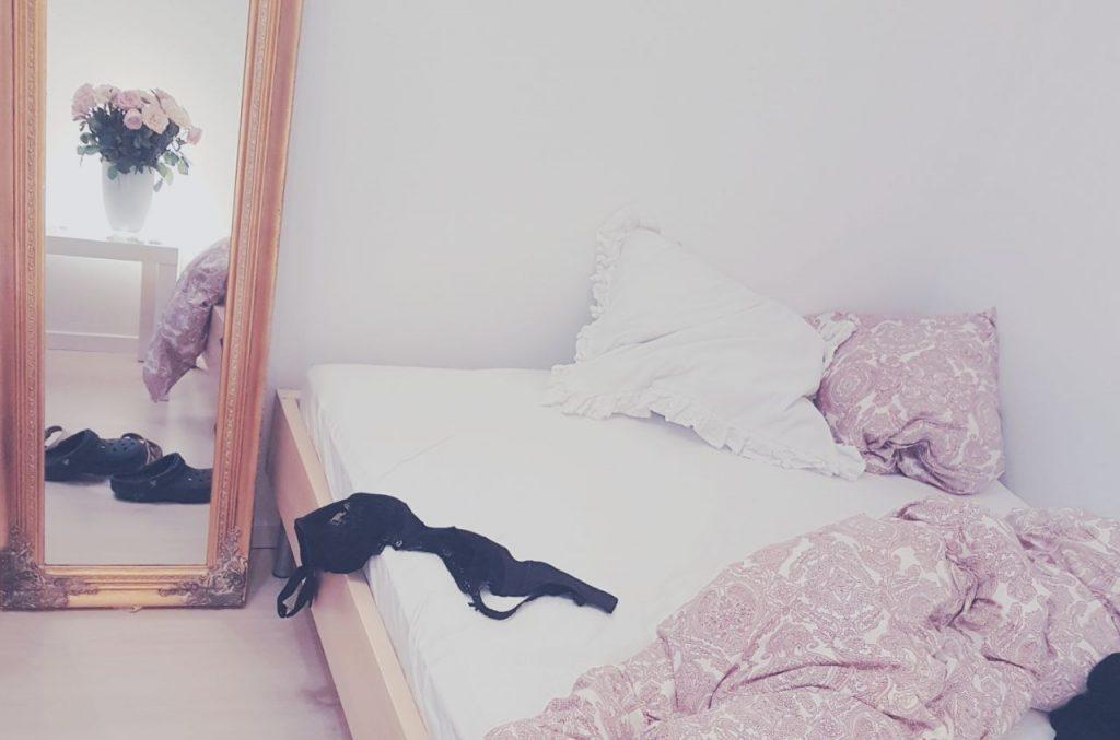 Lust, aufgeschlagenes Bett darauf ein schwarzer BH, daneben ein goldener Spiegel