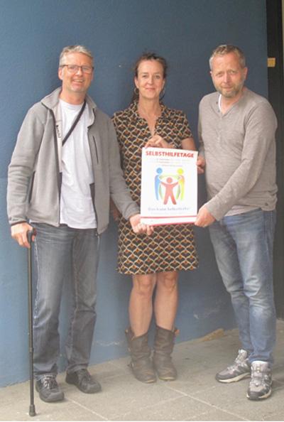 Drei Personen halten eine Broschüre