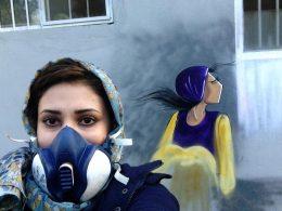 Frau mit Atemmaske und Kopftuch vor einer bemalten Wand.