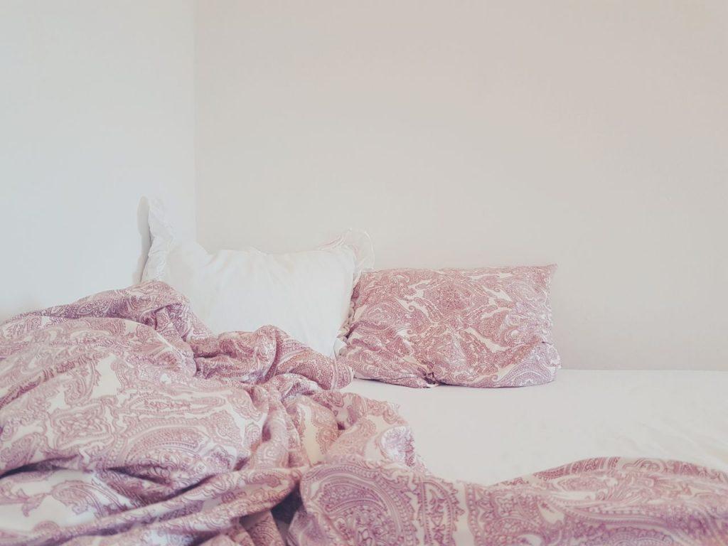 Ein weißes und ein gemustertes Kissen nebeneinander gelgen, leicht an der Wand angelehnt. Davor eine zerknautschte Decke. Matratze ist weiß.