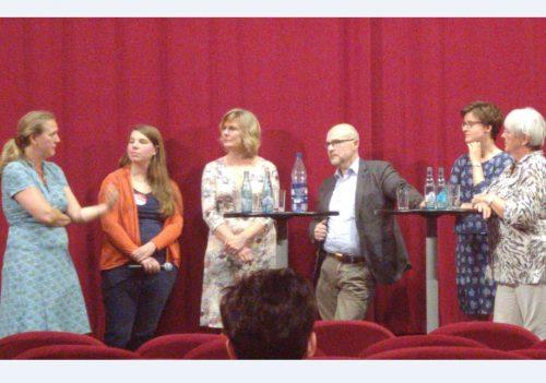 Vor einem roten Vorhang stehen sechs Menschen und diskutieren angeregt über Geburtshelfer*innen in Bremen.