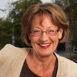 Portrait einer Politikerin mit Brille und rot-geschminkten Lippen. Sie hat braune Haare und trägt ein beiges Jacket. Gudrun Schyman.