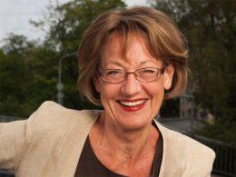 Portrait einer Politikerin mit Brille und rot-geschminkten Lippen. Sie hat braune Haare und trägt ein beiges Jacket.