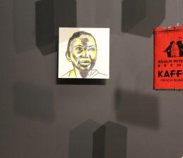 Ein Bild an einer grauen Wand mit einer person of color, am rechten Rand die Hälfte eines roten Bildes