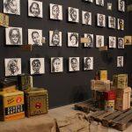 """Bilder an einer grauen Wand mit people of color, im Vordergrund alte Kolonialwaren, der Ausstellung """"Der blinde Fleck"""""""