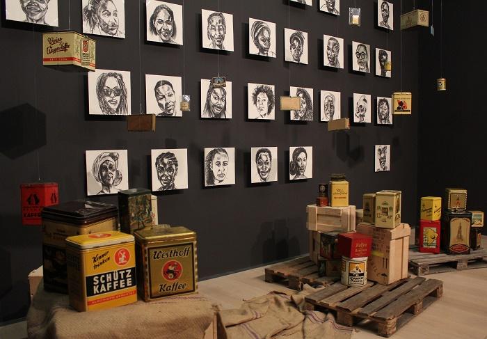 Bilder an einer grauen Wand mit people of color, im Vordergrund alte Kolonialwaren