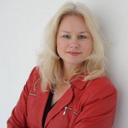 Politikerin mit blonden Haren und roter Jacke
