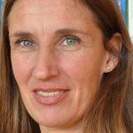 Portrait von Marion Touray, einer frau, die den betrachter*innen direkt in die Augen schaut. Blodnd Haare, grüne Augen, zartes Lächeln