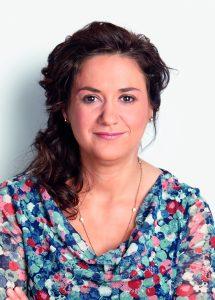 Portraitfoto einer Frau mit braunen Haaren und einer bunten Bluse Sarah Ryglewski