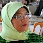 malay Frau mit Kopftuch und Brille sitzend