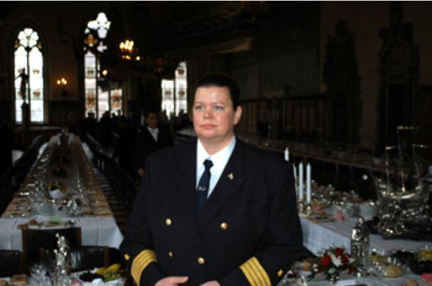 Kapitänin in Uniform mit dunklen Haaren in festlich geschmücktem Saal