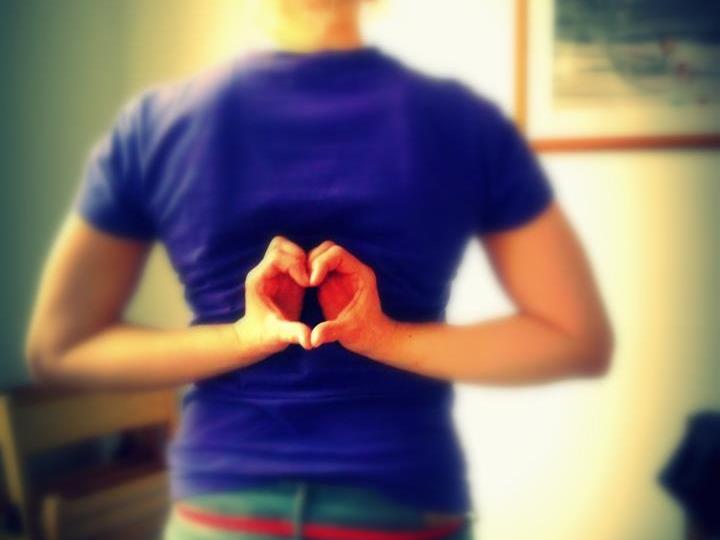 Frau hält ihre Hände zu einem Herz geformt vor ihren Körper