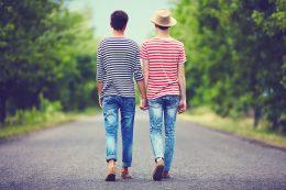 Junges homosexuelles Paar geht Hand in Hand auf einer Straße LSVD