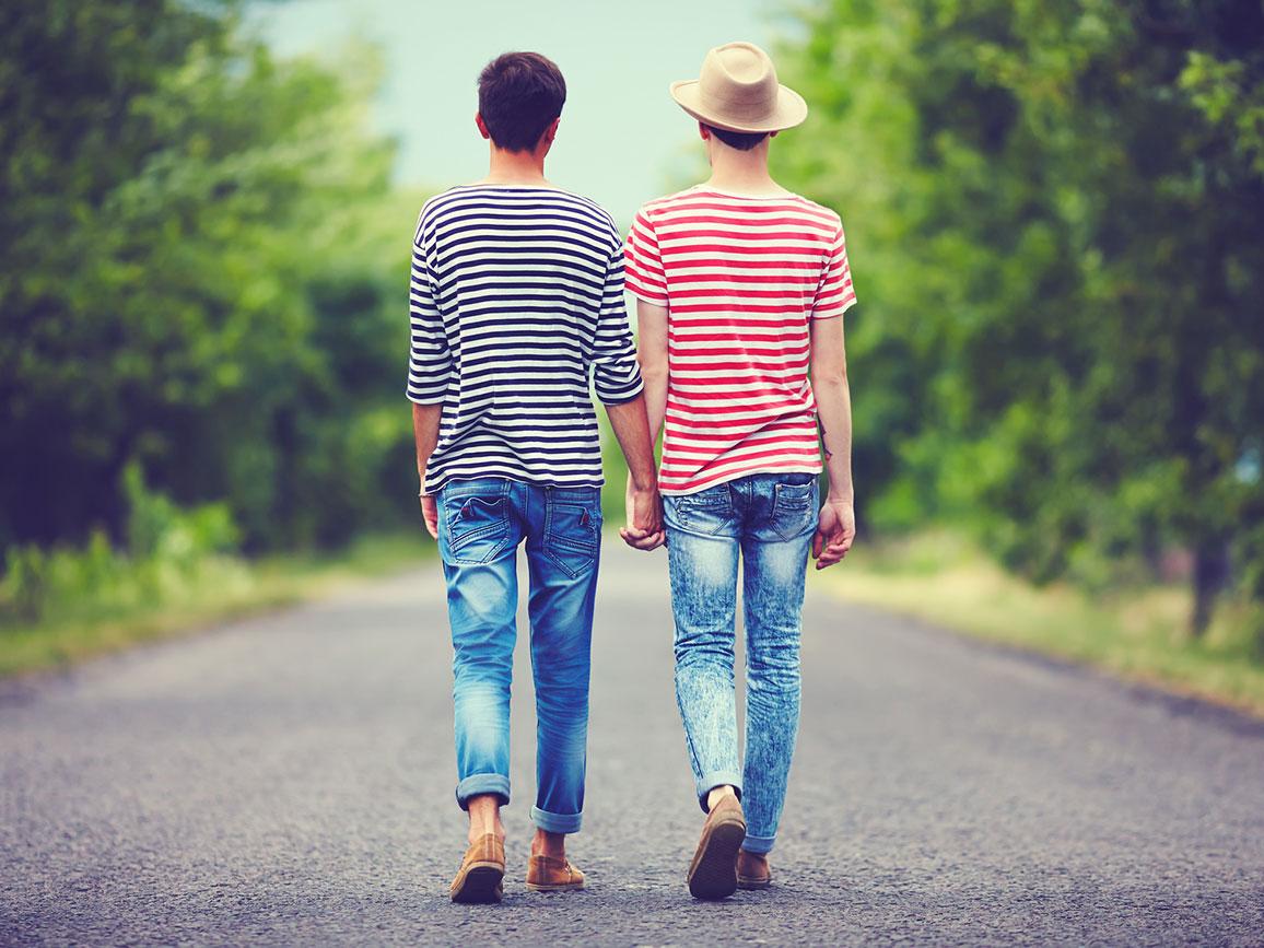 Junges homosexuelles Paar geht Hand in Hand auf einer Straße