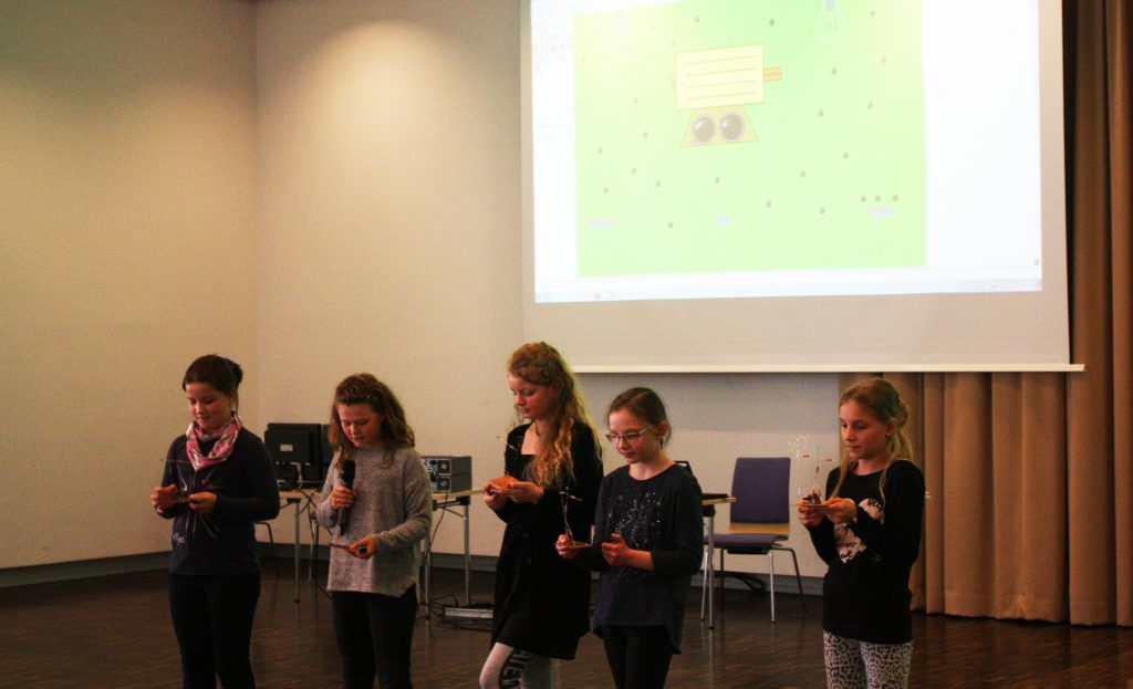 Schnupperstudium, Mädchen auf der Bühne, in der Hand halten sie windmühlenartige Gebilde