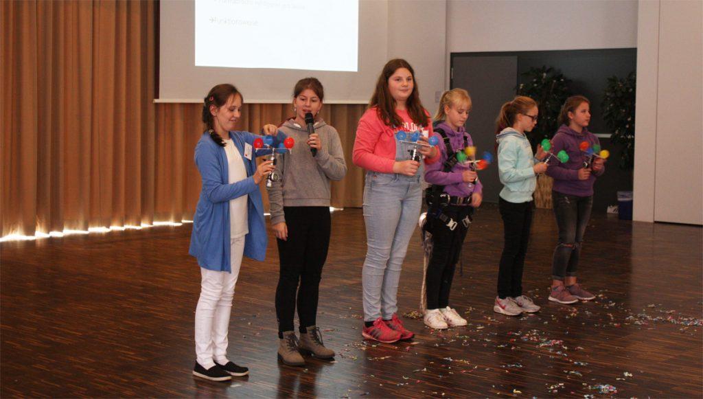 Mädchen auf der Bühne, in der Hand halten sie windmühlenartige Gebilde