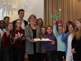 Schnupperstudium, Viele Mädchen mit einigen Erwachsenen auf der Bühne. In der Mitte Ulrike Hauffe mit einem Tablett voller Kerzen.
