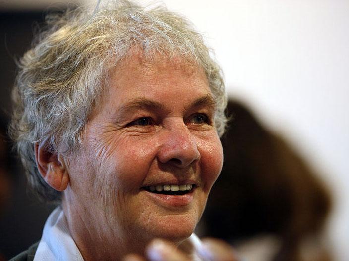 Portrait einer Frau mit kurzen grauen Haaren, lächelnd