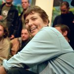 Martha Cooper, lächelnde Frau sitzend im Vordergrund, hinter ihr unscharfe Menschen