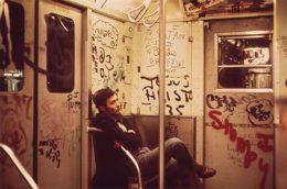 dunkel gekleideter Mann sitzt in U-Bahn, U-Bahn wände sind komplett mit Graffitit bemalt