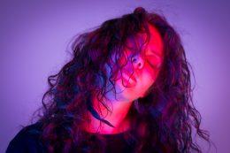 Das Foto zeigt das Gesicht einer Frau. Ihre Augen sind geschlossen und ihren Kopf hält sie etwas seitlich. Es sieht aus als würde sie etwas geniessen. Ihre leicht lockigen Haare trägt sie offen und einige Strähnen fallen ihr leicht ins Gesicht. Der Hintergrunf ist lila. Ihr Gesicht ist pink angeleuchtet.