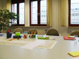 Ein Tisch an dem vier Stühle stehen. Auf dem Tisch sind Essen und Getränk, Stifte, Mappen und Papier. Im Hintergrund sind Fenster und eine Pflanze in der rechten Ecke vom Projekt JobKick PLUS