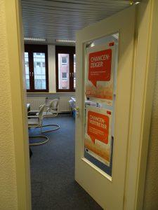 Eine offene Tür mit zwei Plakaten, die die Aufschrift Chancenvertreter und Chancenzeiger haben vom Projekt JobKick PLUS