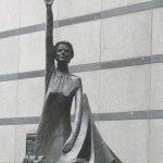 Europa-Statue, Frau hält mit erhobenem Arm ein €-Zeichen