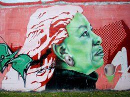 Realistisches Wandgraffiti von Toni Morrison. Sie blickt nach rechts, ihr Gesicht leicht nach oben gerichtet. Ihr Gesichtsausdruck ist bedächtig.