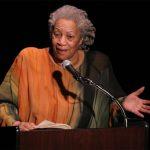 Ein Foto von Toni Morrison, die vor einem Pult, mit Mikrofon. Sie spricht in dieses hinein. Auf dem Pult liegt ein Buch. Hinter ihr ist ein schwarzer Hintergrund.